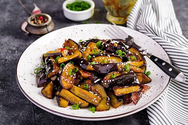 Scharfe würzige eintopf-aubergine im koreanischen stil mit frühlingszwiebeln Premium Fotos