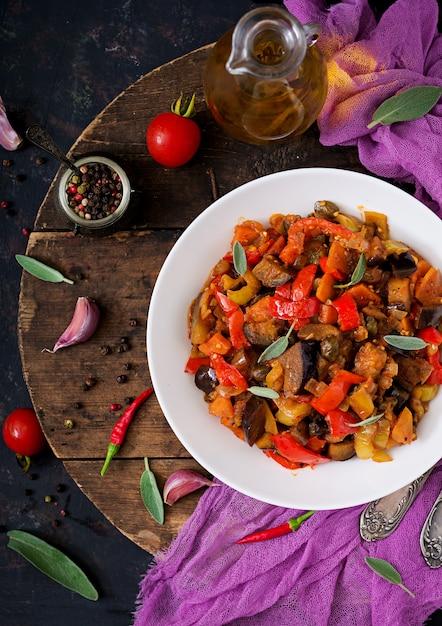 Scharfe würzige eintopf-auberginen, paprika, tomaten und kapern. flach liegen. draufsicht Premium Fotos