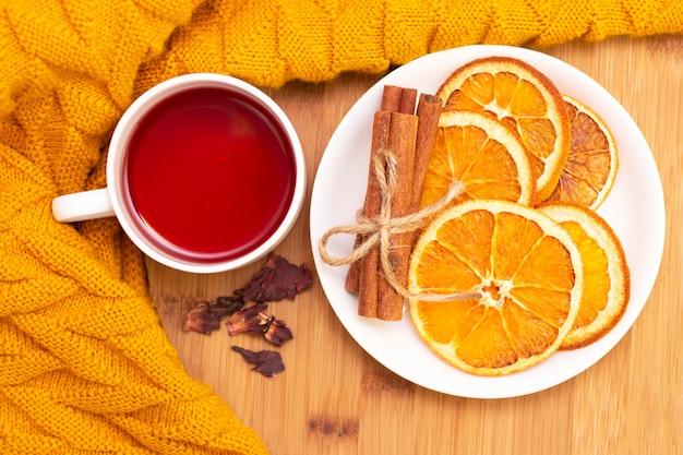 Scharfer aromatischer tee mit zimtstangen und getrockneten orangenscheiben. auf einem holztisch Premium Fotos