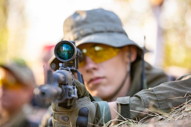 Scharfschütze, bewaffnet mit großkalibrigem scharfschützengewehr, schießt aus dem schutz auf feindliche ziele und sitzt im hinterhalt Premium Fotos