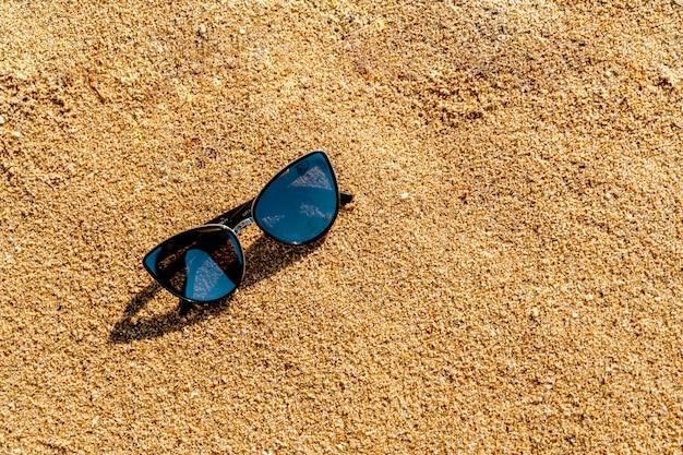 Schatten auf gelbem sand am strand. sommerferien-konzept. brillenschutz vor uv-strahlung Premium Fotos