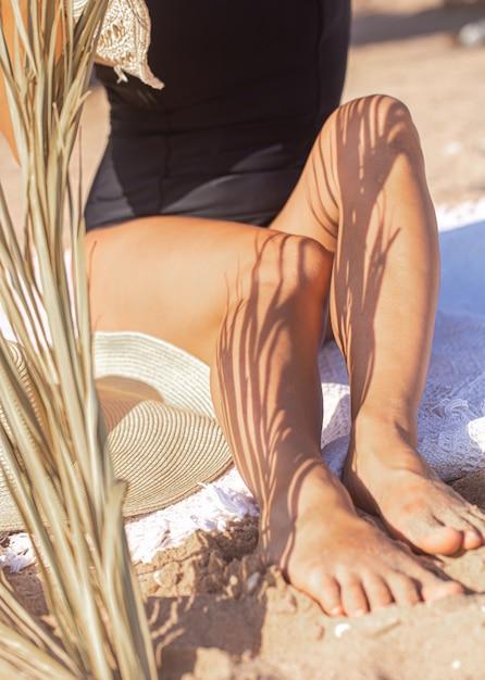 Schatten der palmenzweige auf dem körper einer frau, die sich am strand entspannt. ruhe- und sommerkonzept. Kostenlose Fotos