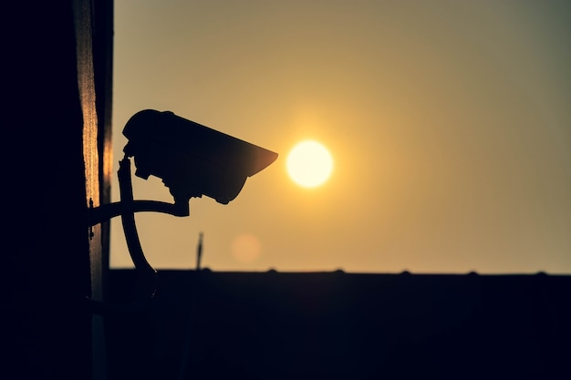 Schattenbild der cctv-überwachungskamera außerhalb des gebäudes morgens mit sonnenhintergrund Premium Fotos