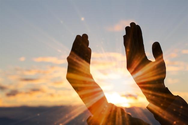 Schattenbild der christlichen betenden mannhand, der geistigkeit und der religion, mann, der zum gott betet. Premium Fotos