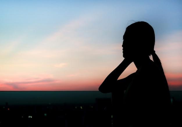 Schattenbild der frau entspannen sich bei sonnenuntergang auf dachspitze des gebäudes. Premium Fotos
