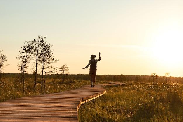 Schattenbild der frau mit rucksack auf wanderweg im sommer im freien. naturforscher genießt die natur und einen moment bei sonnenuntergang auf dem weg Premium Fotos