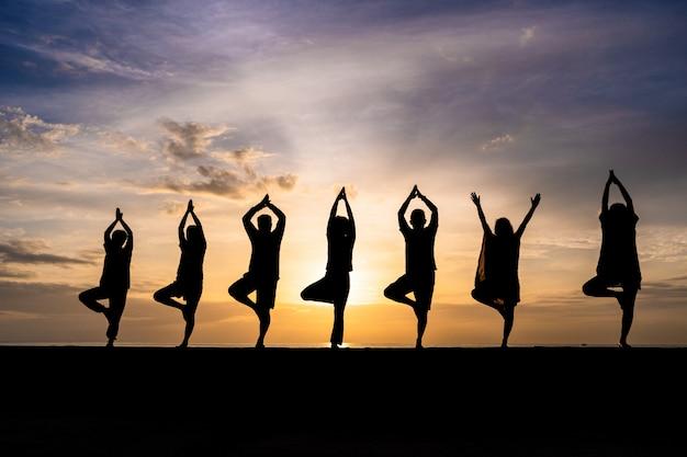 Schattenbild der gruppe von personen yoga während des bunten sonnenuntergangs oder des sonnenaufgangs an einem strand tuend Premium Fotos