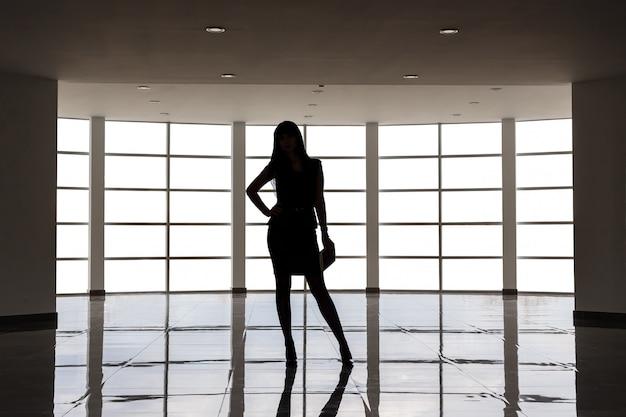 Schattenbild der jungen attraktiven frau, die im anzug mit einem kurzen rock gekleidet wird, steht gegen das große leere fenster in einem weißen büro und hält ein anmerkungsbuch. Premium Fotos