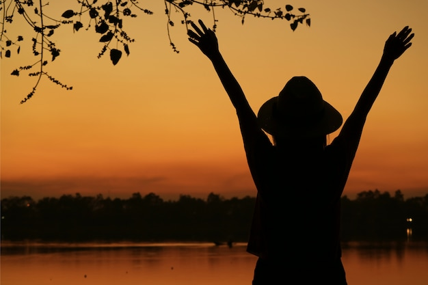Schattenbild der jungen frau arme gegen schönen orange farbsonnenunterganghimmel auf dem seeufer anhebend Premium Fotos