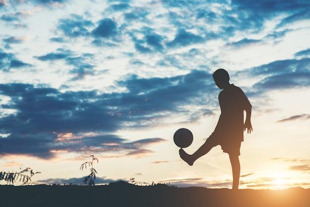 Schattenbild der kinder spielen fußballfußball Kostenlose Fotos
