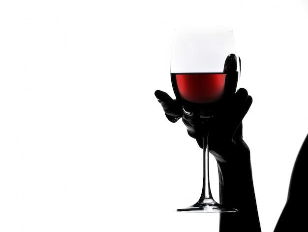Schattenbild der nahaufnahmefrau hand, das ein glas wein hält. Premium Fotos