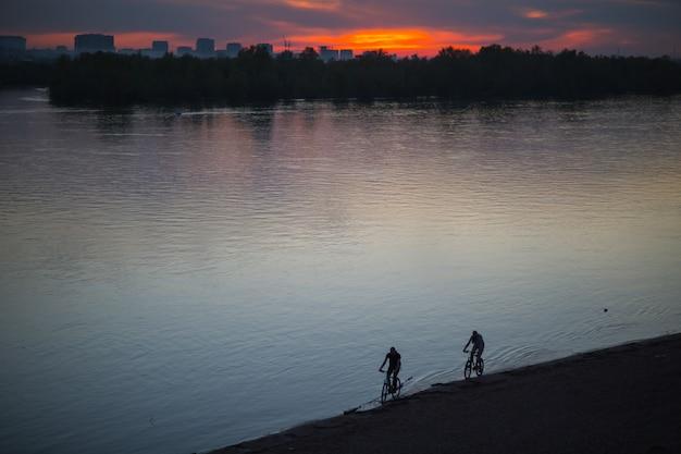 Schattenbild der radfahrer, die ein rennrad am sonnenuntergang im strandfluss reiten Premium Fotos