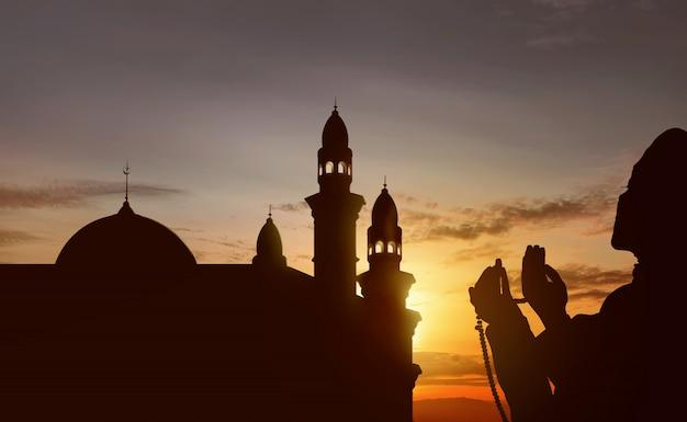 Schattenbild des asiatischen moslems betend mit gebetsperlen Premium Fotos