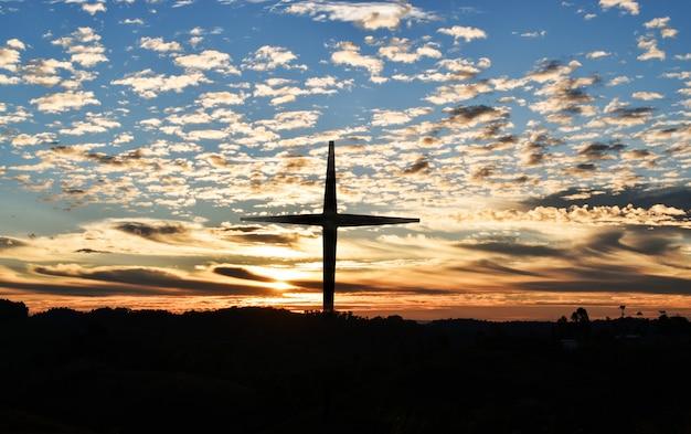 Schattenbild des christlichen kreuzes und der windkraftanlagen bei sonnenuntergang Premium Fotos