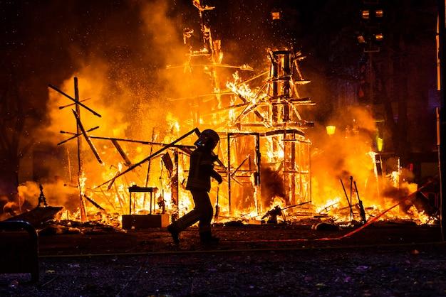 Schattenbild des feuerwehrmannes versuchend, ein feuer in einer straße während einer nacht zu steuern. Premium Fotos