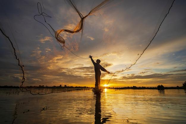 Schattenbild des fischers auf fischerboot mit netz auf dem see bei sonnenuntergang Premium Fotos
