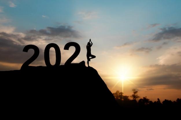 Schattenbild des glücklichen neuen jahres 2021 mit frau, die yoga tut Premium Fotos