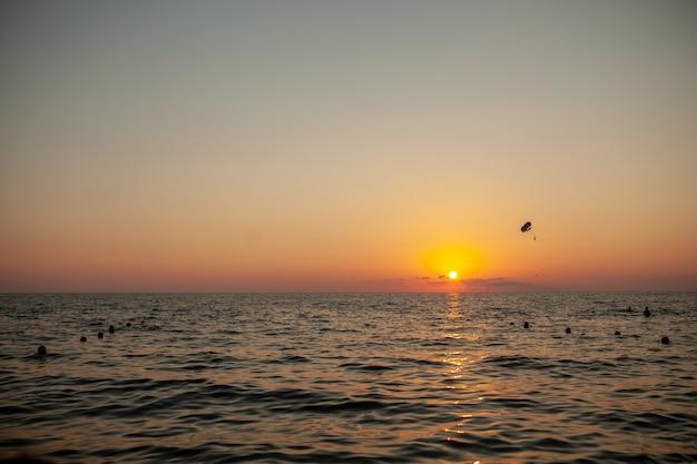Schattenbild des hochfliegenden fluges des angetriebenen gleitschirms über dem meer gegen erstaunlichen orange sonnenunterganghimmel. Premium Fotos