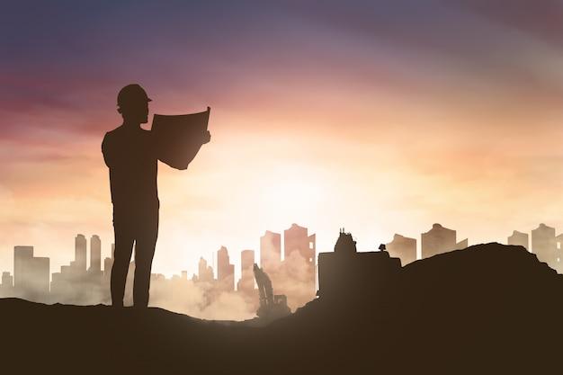 Schattenbild des ingenieurmannes seinen plan in der baustelle schauend Premium Fotos