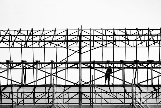 Schattenbild des ingenieurs stehend, sicher an hoher struktur des gebäudes zu arbeiten Premium Fotos