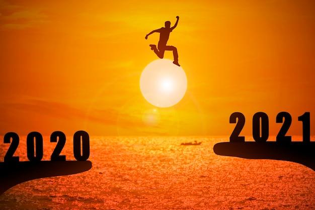 Schattenbild des jungen mannes, der zwischen 2020 und 2021 jahren mit schönem sonnenuntergang am meer springt. Premium Fotos