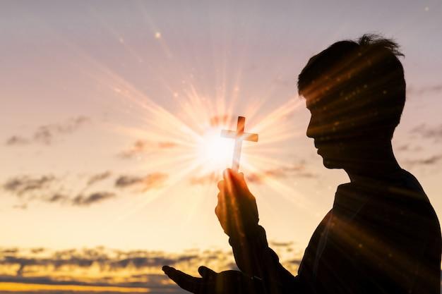 Schattenbild des kreuzes in der menschlichen hand, der hintergrund ist der sonnenaufgang. Premium Fotos