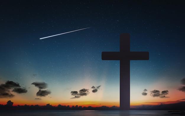 Schattenbild des kruzifixkreuzes zur sonnenuntergangzeit und zum nächtlichen himmel mit sternschnuppenhintergrund. Premium Fotos