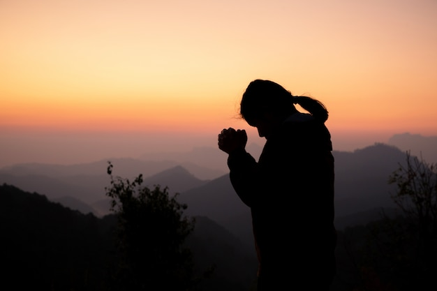 Schattenbild des mädchens betend über schönem himmelhintergrund. Kostenlose Fotos