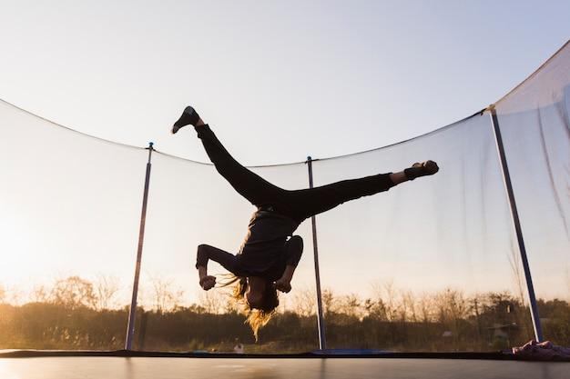 Schattenbild des mädchens springend auf eine trampoline, die spalte tut Kostenlose Fotos