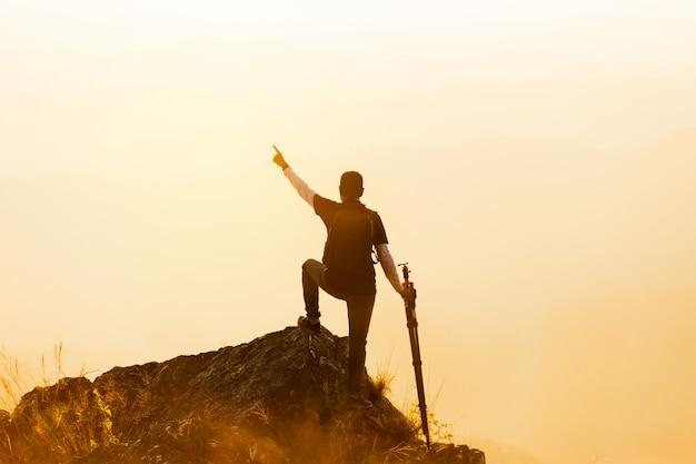 Schattenbild des mannes halten hände auf der spitze des berges, erfolgskonzept hoch Premium Fotos