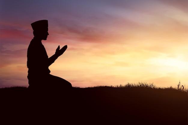 Schattenbild des moslemischen mannes betend Premium Fotos