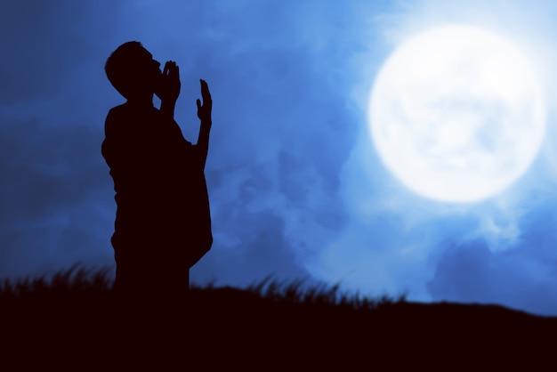 Schattenbild des muslimischen mannes in ihreram kleidung, die steht und betet, während erhobene arme Premium Fotos
