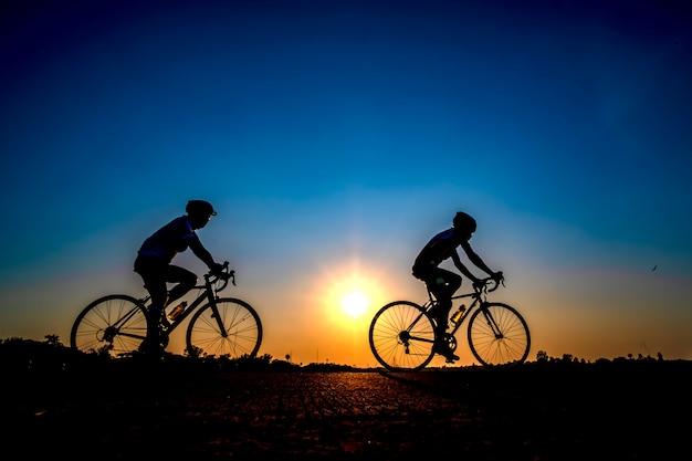 Schattenbild des radfahrers im sonnenunterganghintergrund. Premium Fotos
