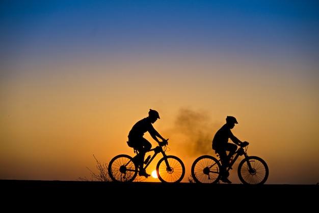 Schattenbild des radfahrers mit mountainbike auf schöner sonnenuntergangzeit Premium Fotos
