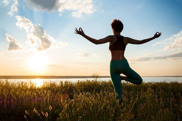 Schattenbild des sportlichen mädchens, das yoga im feld bei sonnenaufgang praktiziert. Kostenlose Fotos