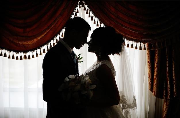 Schattenbild einer braut und des bräutigams auf dem hintergrund des fensters. braut und bräutigam küssen auf dem hintergrund des fensters. Premium Fotos