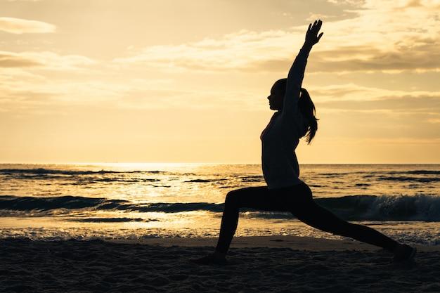 Schattenbild einer frau am strand während des morgens trainiert bei sonnenaufgang Premium Fotos