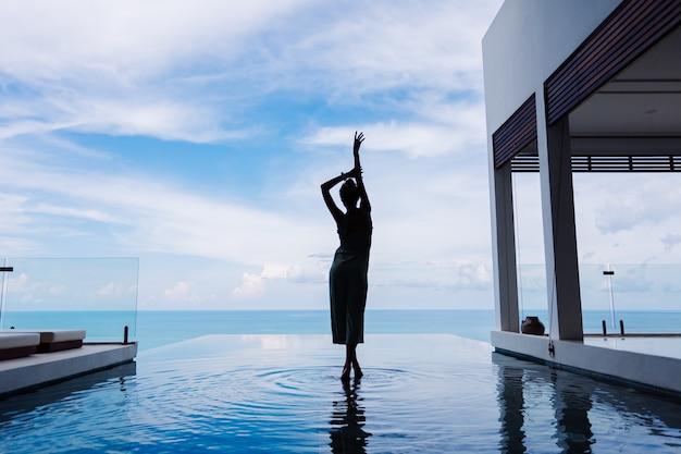 Schattenbild einer frau, die auf der wasseroberfläche des unendlichkeitspools einer teuren reichen luxusvilla auf einem berg mit meerblick geht Kostenlose Fotos