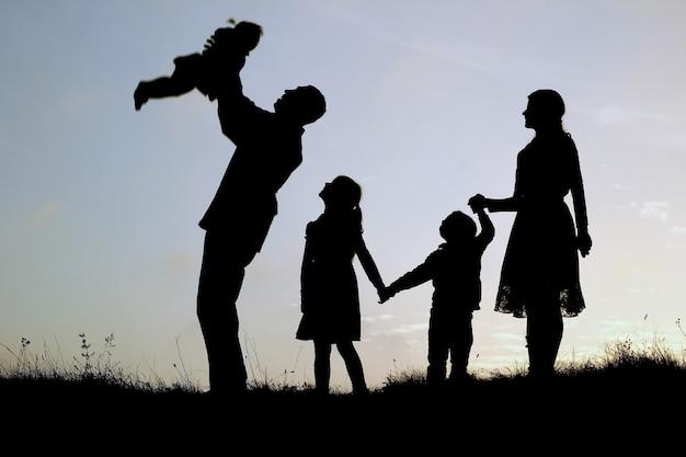 Schattenbild einer glücklichen familie mit kindern auf natur Premium Fotos