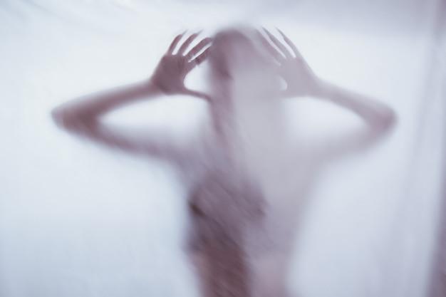 Schattenbild einer weiblichen sexuellen zahl hinter nebeligem glas. konzept des geistes des poltergeists von der anderen welt. erschreckende hände des todes durch den stoff. Premium Fotos