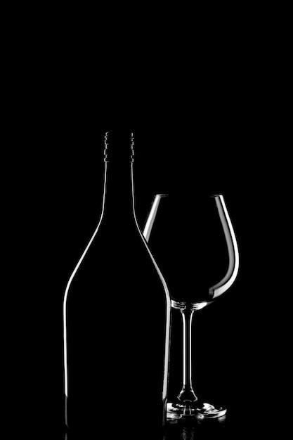 Schattenbild einer weinflasche und des weinglases auf schwarzem hintergrund Premium Fotos