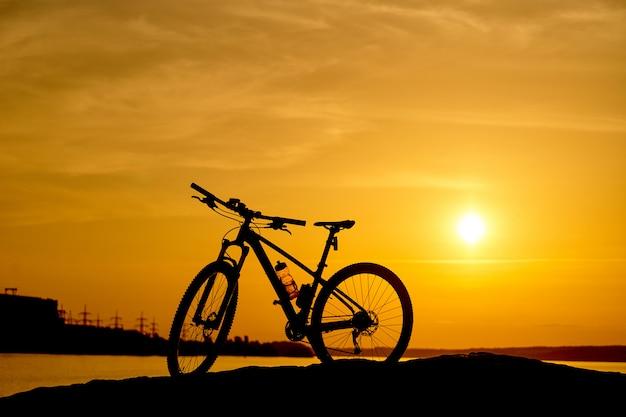 Schattenbild eines fahrrades am sonnenuntergang Premium Fotos