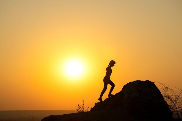 Schattenbild eines frauenwanderers, der einen großen stein bei sonnenuntergang in den bergen klettert. weiblicher tourist auf hohem felsen in der abendnatur. konzept für tourismus, reisen und gesunden lebensstil. Premium Fotos