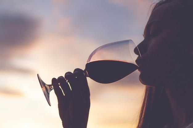 Schattenbild eines jugendlichen, der ein glas wein bei sonnenuntergang am abend sich entspannt, genießt und trinkt. Premium Fotos