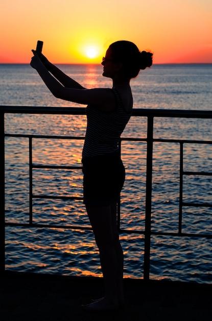 Schattenbild eines jungen mädchens am sonnenuntergang. dämmerung, wellen. mädchen maki Premium Fotos