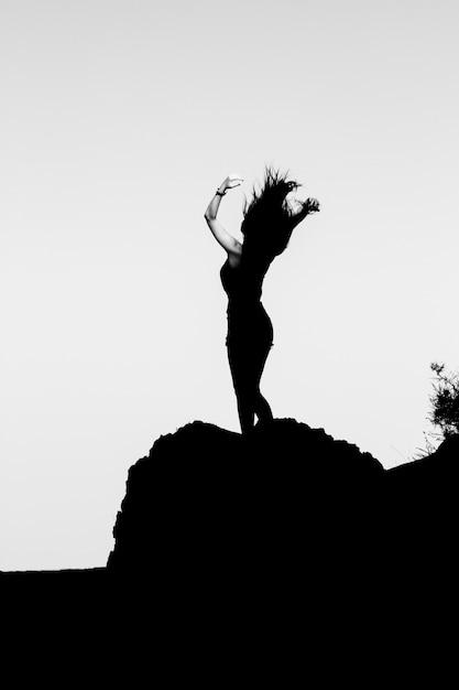 Schattenbild eines mädchens oben auf einen berg. Premium Fotos