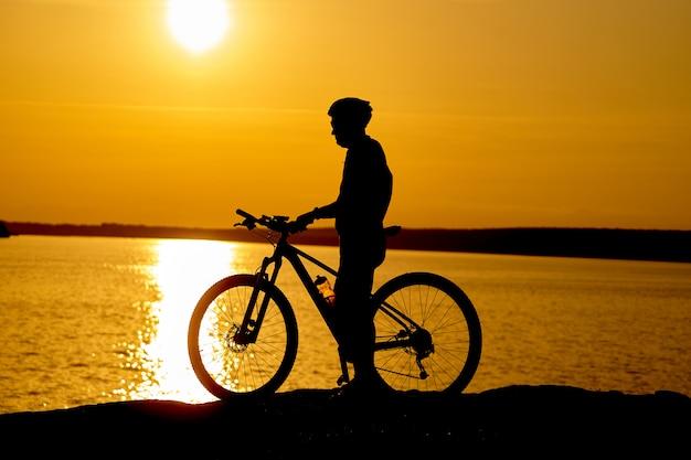 Schattenbild eines männlichen radfahrers mit sturzhelm bei sonnenuntergang nahe dem fluss Premium Fotos