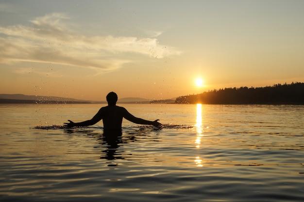 Schattenbild eines mannes am sonnenunterganghintergrund. der kerl an der taille stürzte ins meer. Premium Fotos