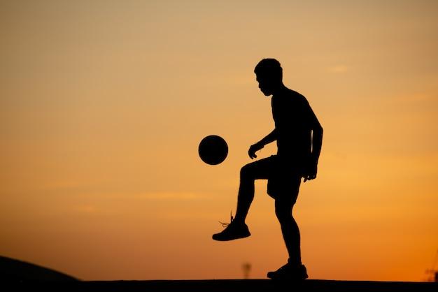 Schattenbild eines mannes, der fußball in der goldenen stunde, sonnenuntergang spielt. Kostenlose Fotos