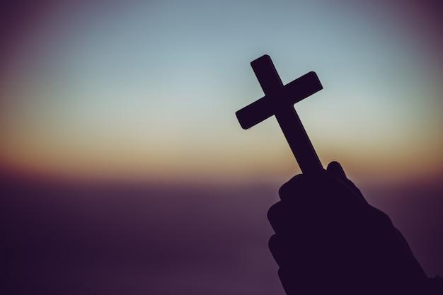 Schattenbild eines mannes, der in der hand mit einem kreuz bei sonnenaufgang betet. Kostenlose Fotos